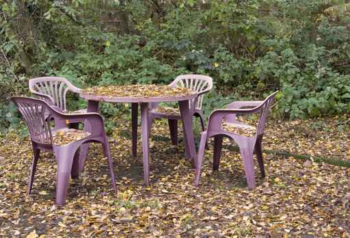 plastic outdoor table and chairs covered with leaves